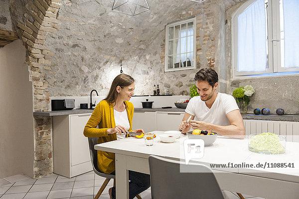 Paar in der Küche bei der Zubereitung von Obstsalat