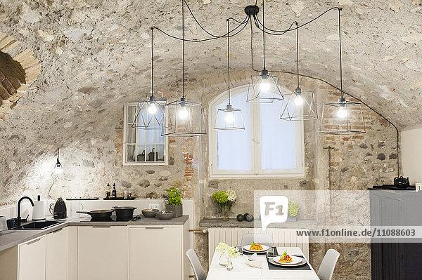 Moderne Küche im alten Steinhaus mit frisch gekochten Nudeln auf dem Tisch