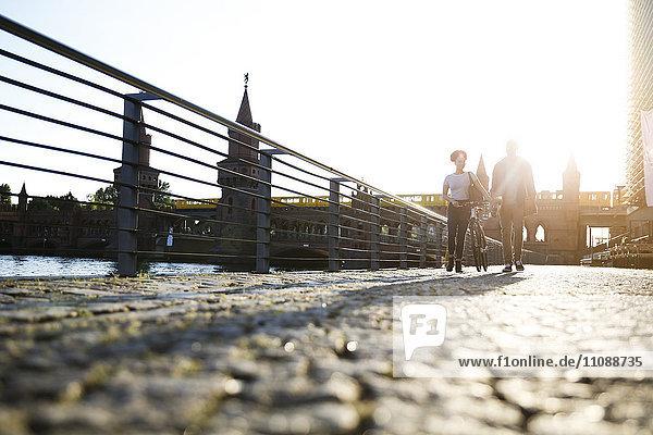 Couple walking by river  pushing bicycle
