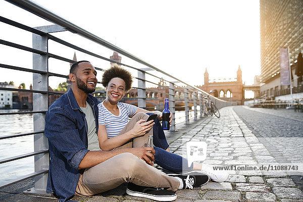 Paar sitzend am Fluss mit Flaschen und Smartphone