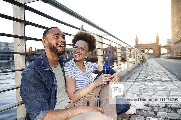 Paar am Fluss sitzend  Flaschen haltend