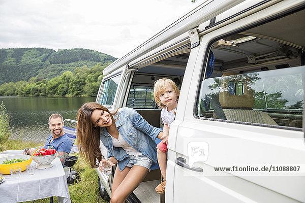 Familie mit Van am Seeufer
