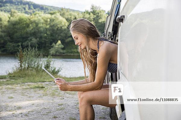 Junge Frau sitzt in einem Transporter am Seeufer mit digitalem Tablett