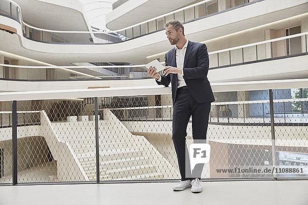 Geschäftsmann mit Tablette im Bürogebäude