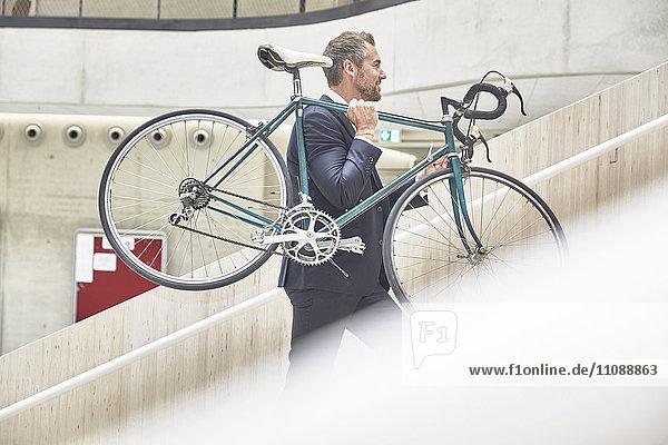 Geschäftsmann mit Fahrrad im Bürogebäude Geschäftsmann mit Fahrrad im Bürogebäude