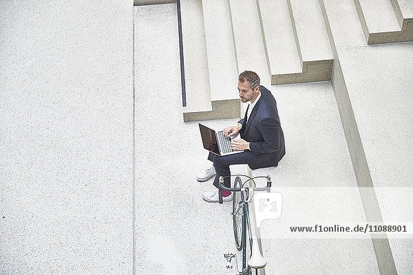 Geschäftsmann auf der Treppe mit Laptop neben dem Fahrrad