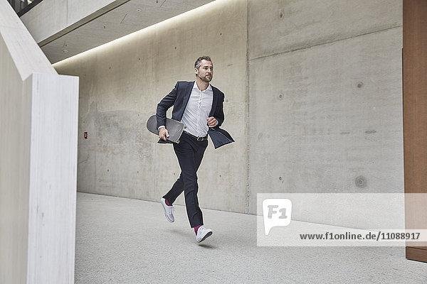 Geschäftsmann läuft mit Skateboard an der Betonwand entlang