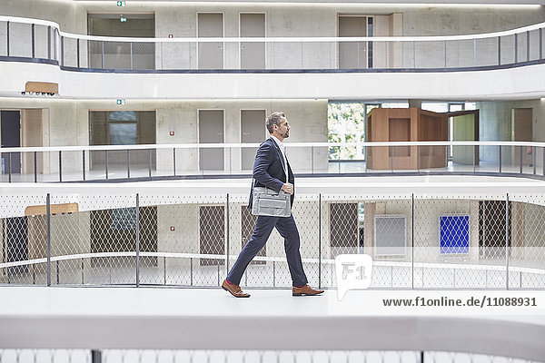 Businesssman walking with bag in modern office building