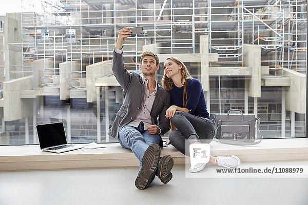Junges Paar sitzt am Fenster und nimmt einen Selfie