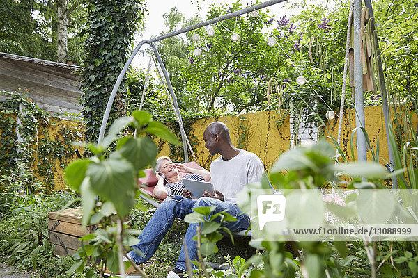Zwei Freunde auf einer Schaukel im Garten beim gemeinsamen Vergnügen
