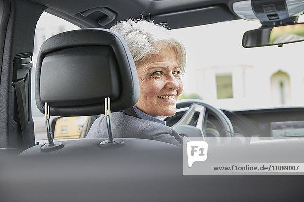 Porträt einer lächelnden Geschäftsfrau im Auto