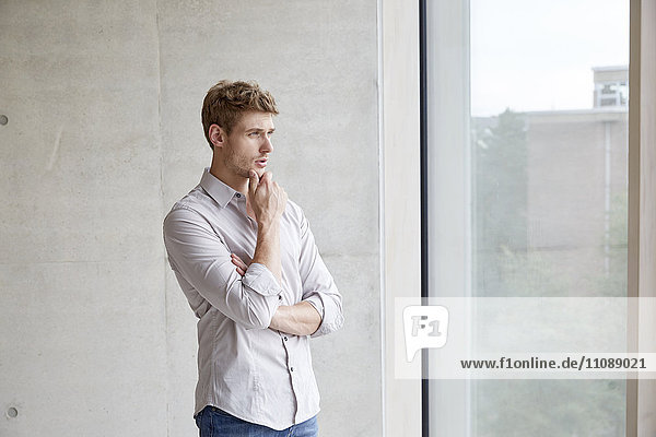 Young man looking out of window