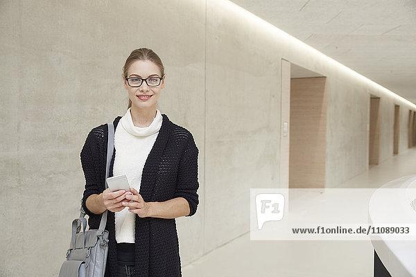 Lächelnde junge Frau auf dem Flur des Gebäudes