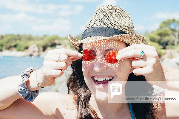 Porträt einer lächelnden Frau mit Strohhut am Strand  die ihre Augen mit Erdbeeren bedeckt.