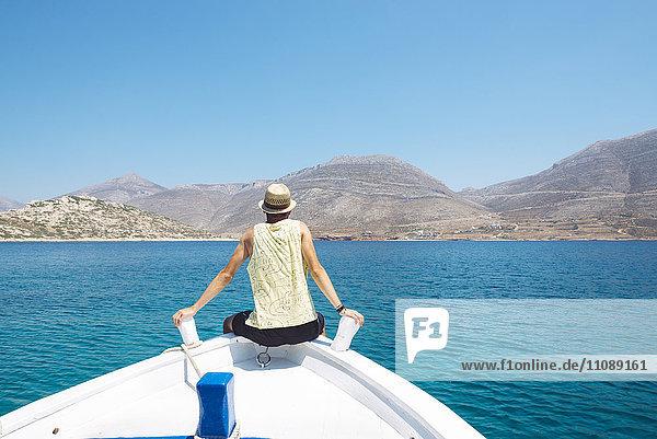 Griechenland  Rückansicht eines Mannes am Bug eines Bootes mit Blick auf die Insel Amorgos