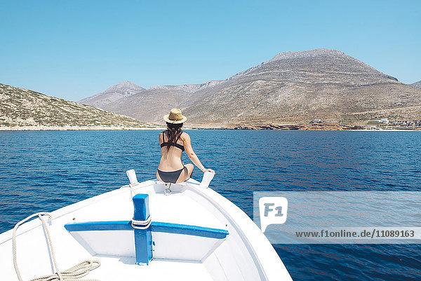 Griechenland  Rückansicht einer Frau am Bug eines Bootes mit Blick auf die Insel Amorgos