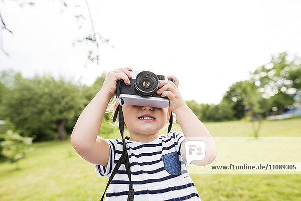 Kleines Mädchen im Park spielt mit der Kamera