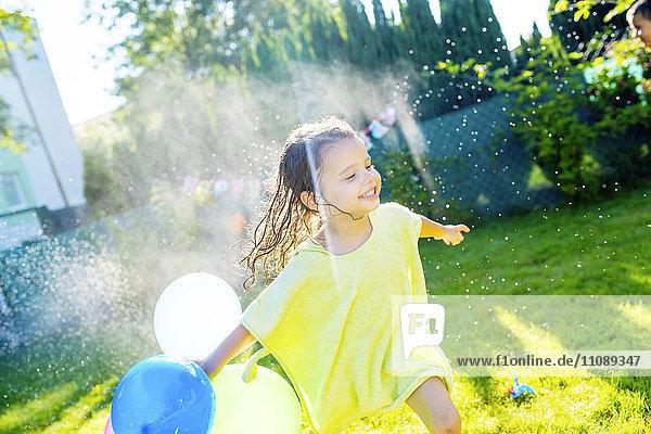 Kleines Mädchen mit Luftballons mit Rasensprenger im Garten Kleines Mädchen mit Luftballons mit Rasensprenger im Garten
