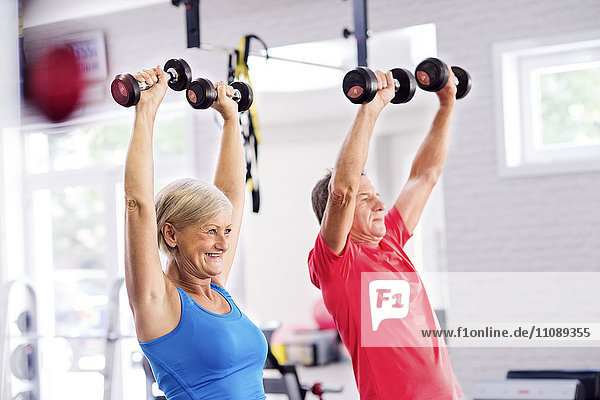 Reife Frau und älterer Mann beim Training im Fitnessstudio