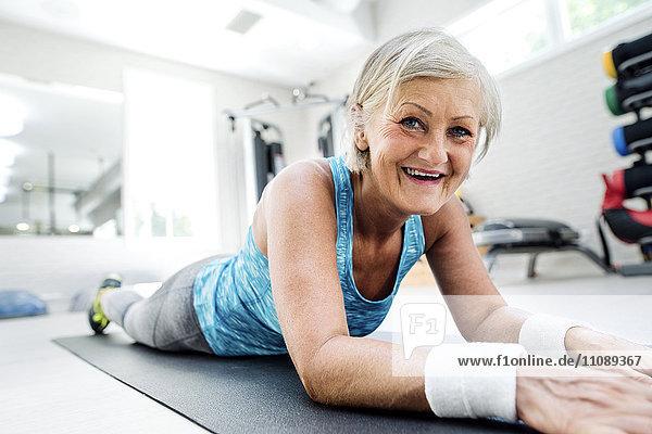Lächelnde reife Frau,  die auf einer Turnmatte im Fitnessstudio liegt.