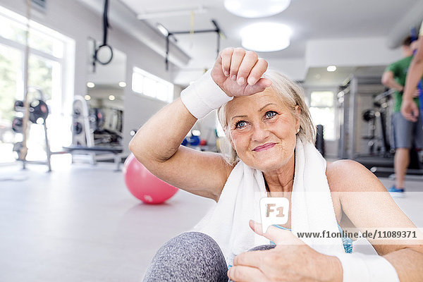 Lächelnde reife Frau bei einer Pause im Fitnessstudio