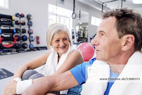 Lächelnde reife Frau und älterer Mann bei einer Pause im Fitnessstudio