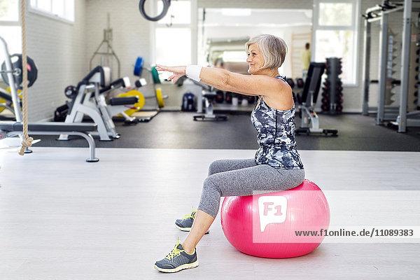 Reife Frau beim Turnen auf dem Fitnessball im Fitnessstudio