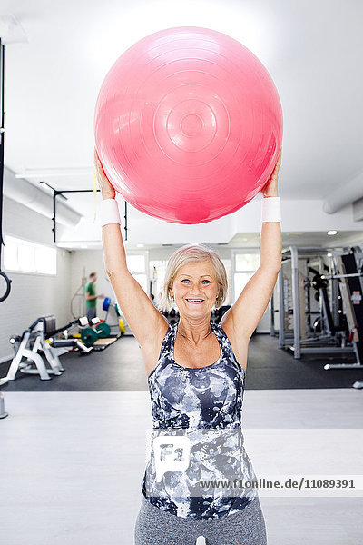 Lächelnde reife Frau hebt Fitnessball in der Turnhalle an