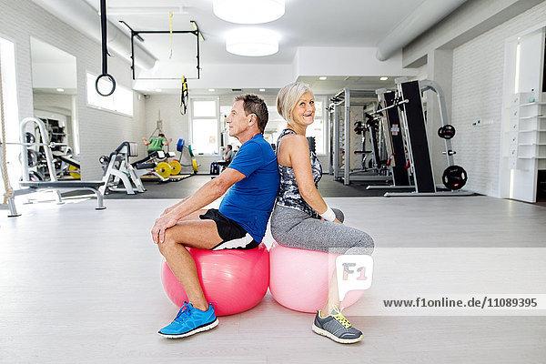 Senior-Mann und reife Frau sitzen auf Fitnessbällen in der Turnhalle