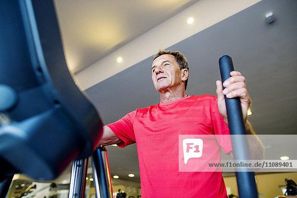 Senior Mann beim Training auf Stepper im Fitnessstudio
