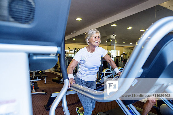 Reife Frau beim Training auf dem Laufband im Fitnessstudio