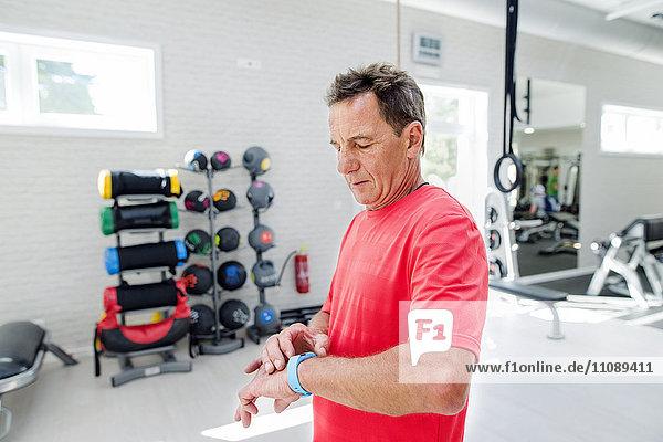 Senior Mann im Fitnessstudio mit Blick auf smartwatch