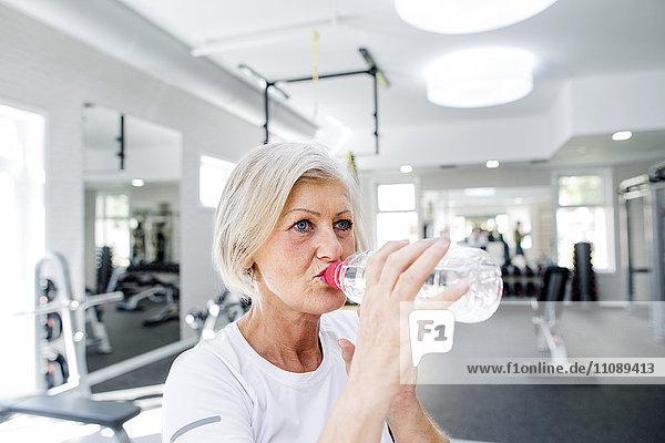Reife Frau im Fitnessstudio Trinkwasser aus der Flasche
