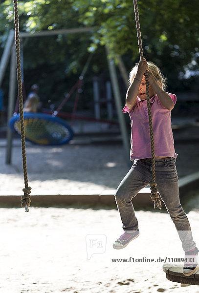 Little girl climbing on a playground