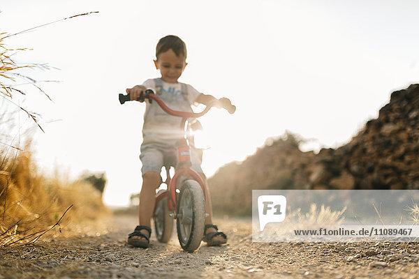 Kleiner Junge mit Kinderfahrrad auf Schotterpiste