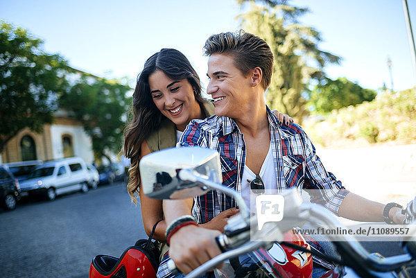 Glückliches junges Paar auf dem Motorrad