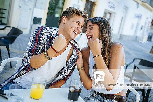 Lachendes junges Paar sitzt im Straßencafé
