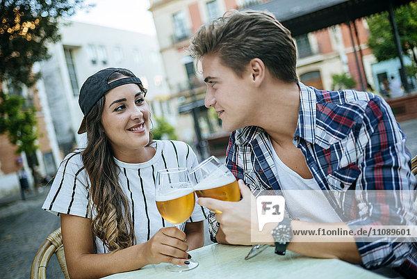 Junges Paar trinkt Bier im Straßencafé
