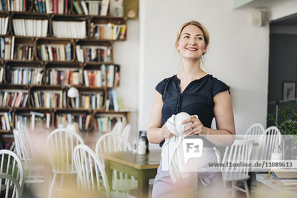 Lächelnde Frau trocknet Tasse in einem Café