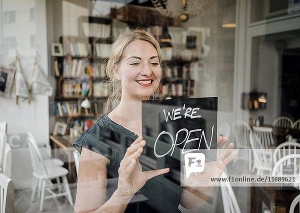 Lächelnde Frau in einem Café mit offenem Schild an der Glasscheibe