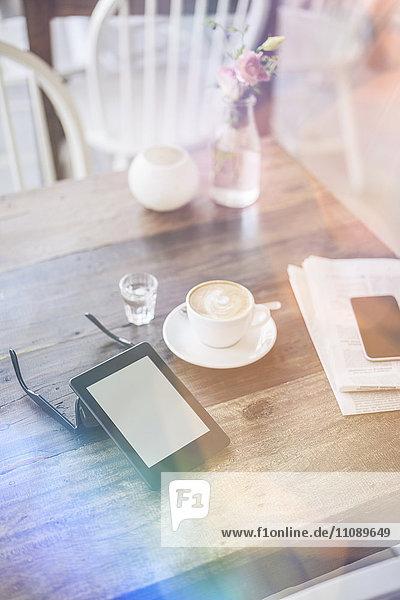 E-Book  Sonnenbrille und Tasse Kaffee auf dem Tisch im Cafe