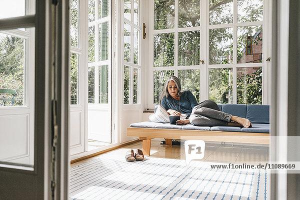 Frau liegt auf der Lounge im Wintergarten und liest E-Book