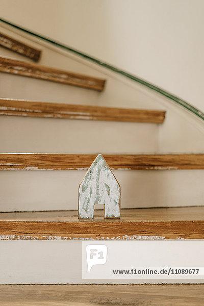Holzstück in Form eines Hauses auf einer Holztreppe stehend Holzstück in Form eines Hauses auf einer Holztreppe stehend