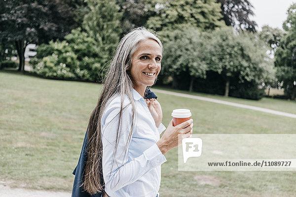 Lächelnde Frau mit Kaffee zum Mitnehmen im Park