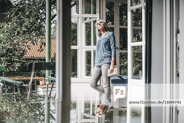 Frau steht vor geöffneter Terrassentür und genießt das Sonnenlicht