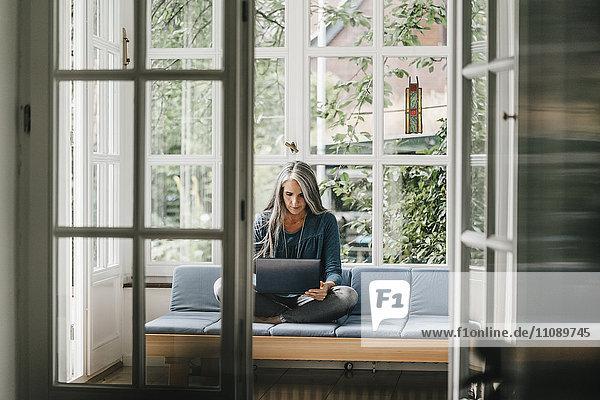Frau sitzt auf der Lounge im Wintergarten mit Laptop