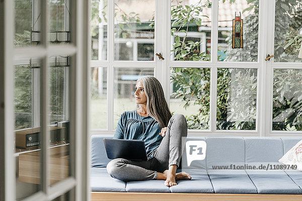 Frau sitzend auf der Lounge im Wintergarten mit Laptop