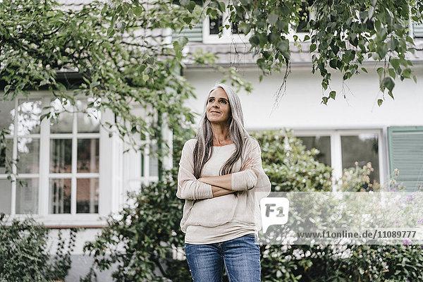 Lächelnde Frau mit langen grauen Haaren im Garten stehend