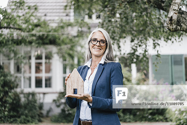 Portrait of smiling businesswoman with piece of wood shaped like a house standing in the garden