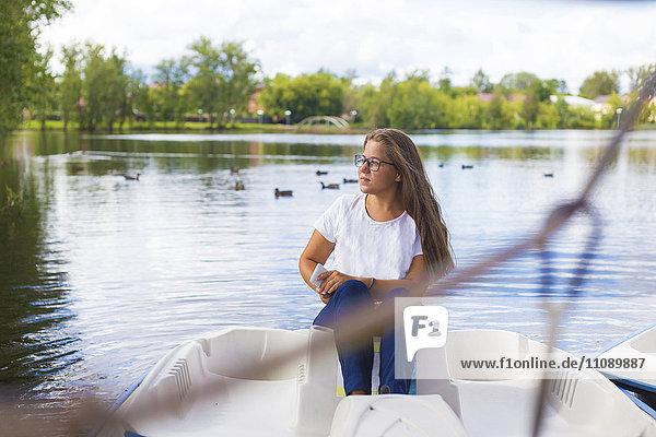 Russland  Tichwin  Teenagermädchen mit Smartphone  im Boot sitzend